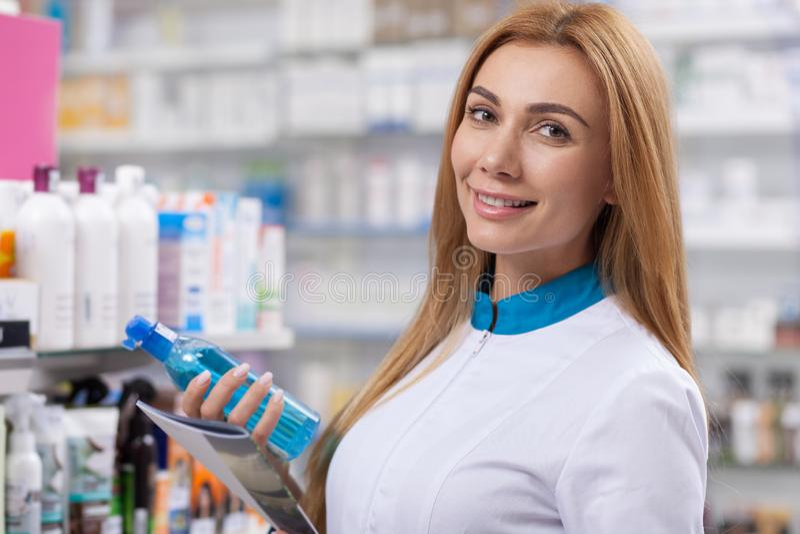 Женский аптекарь работая на ее аптеке стоковое изображение rf