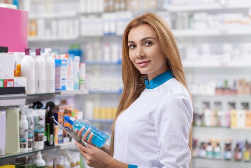 Женский аптекарь работая на ее аптеке стоковая фотография