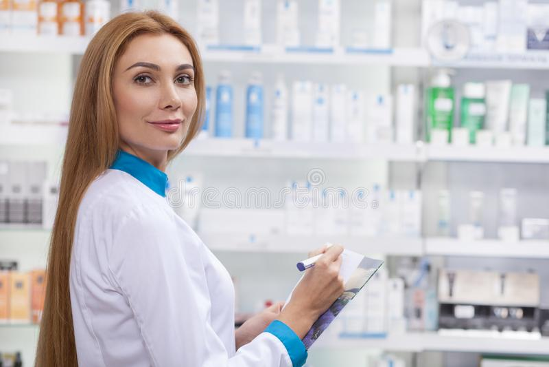 Женский аптекарь работая на ее аптеке стоковые изображения rf