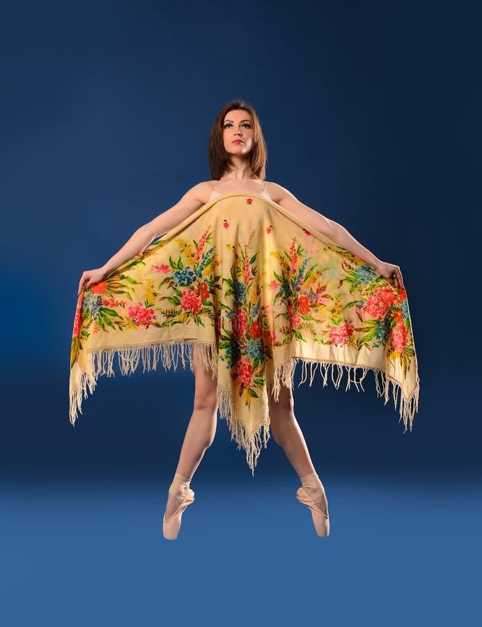 Женский артист балета скача с головным платком стоковое фото