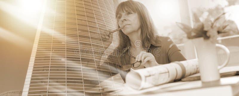 Женский архитектор работая на планах, светлое effet; множественная выдержка стоковое изображение rf