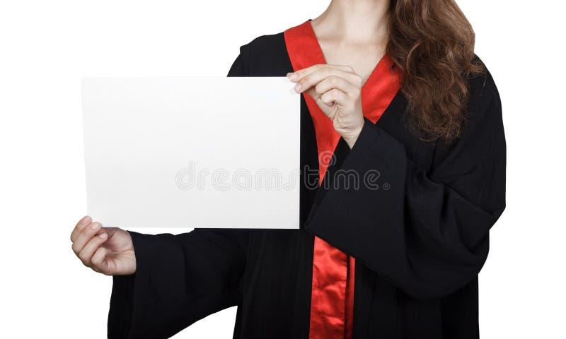 Женский аспирант peeking от за пустой панели Портрет счастливой девушки в мантии градации с доской плаката, стоковая фотография