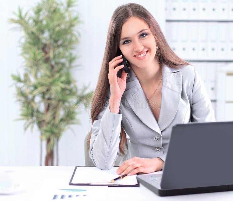 Женский ассистентский говорить на телефоне сидя за столом стоковая фотография rf