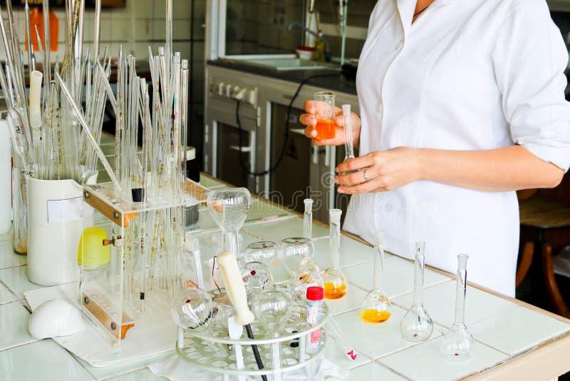 Женский ассистент лаборатории, доктор, химик, работы с склянками, пробирками, делает решения, медицины, ингридиенты смешиваний стоковые фото