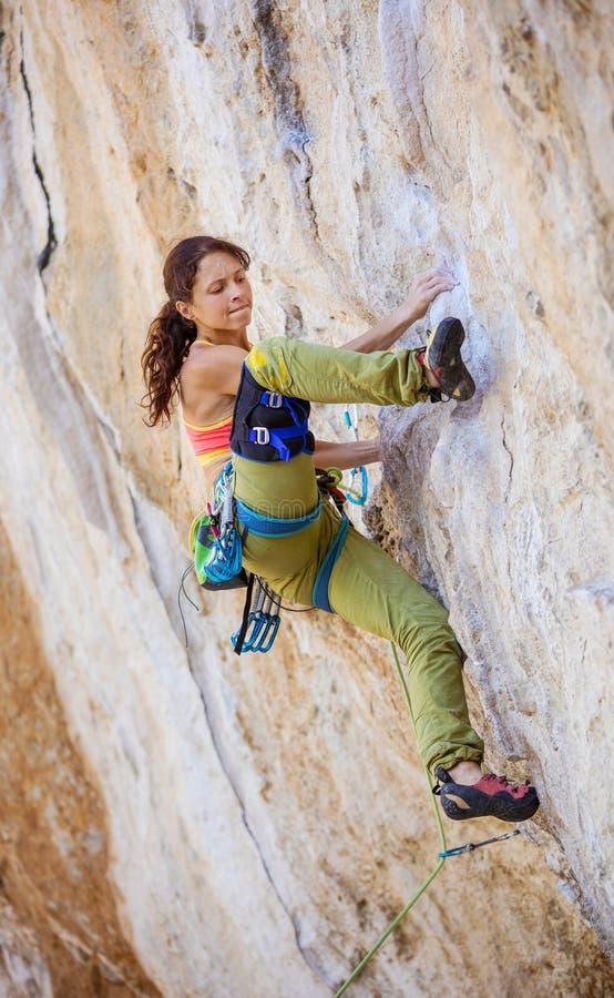 Женский альпинист утеса на трудной трассе на скале стоковое изображение rf