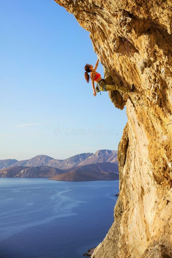 Женский альпинист утеса на трудной трассе стоковые изображения