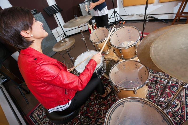 Женский барабанщик выполняя в студии звукозаписи стоковое изображение rf