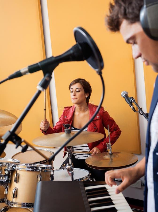 Женский барабанщик выполняя с мужским пианистом стоковые изображения rf