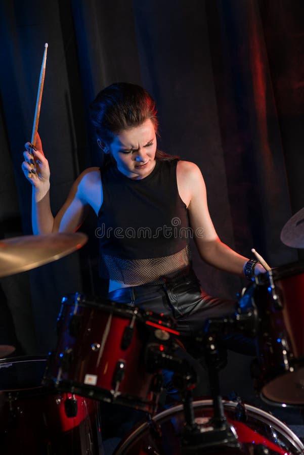 Женский барабанщик играя барабанчики стоковое фото