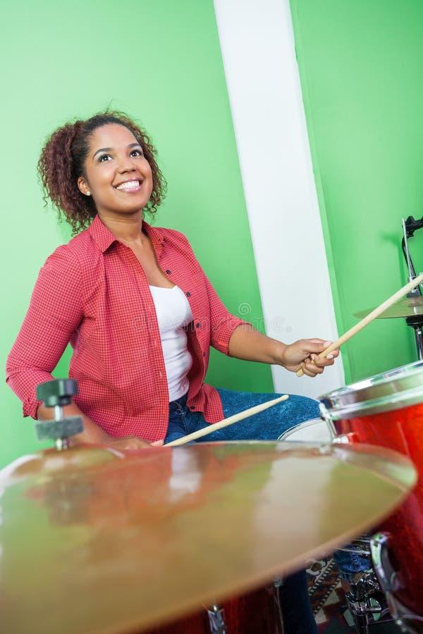 Женский барабанщик смотря вверх пока выполняющ стоковое фото rf