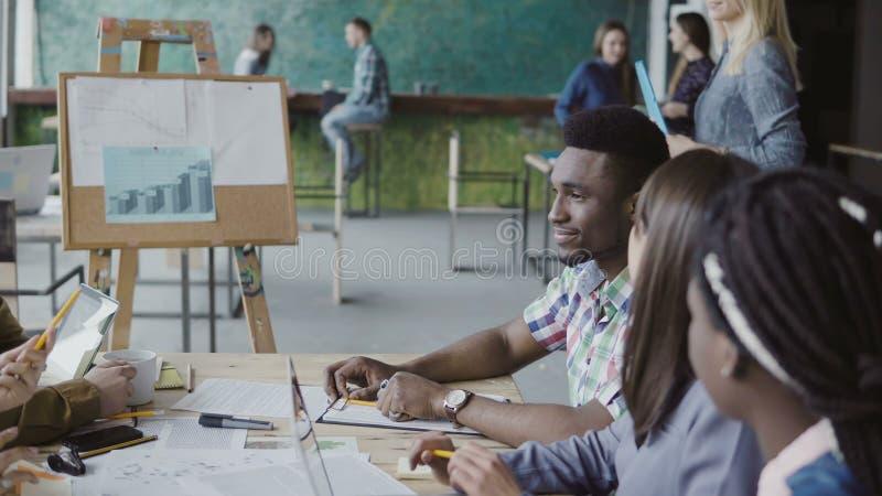 Женский белокурый менеджер приходит к молодой команде дела Multiracial групповая встреча группы людей в ультрамодном офисе битник стоковая фотография rf