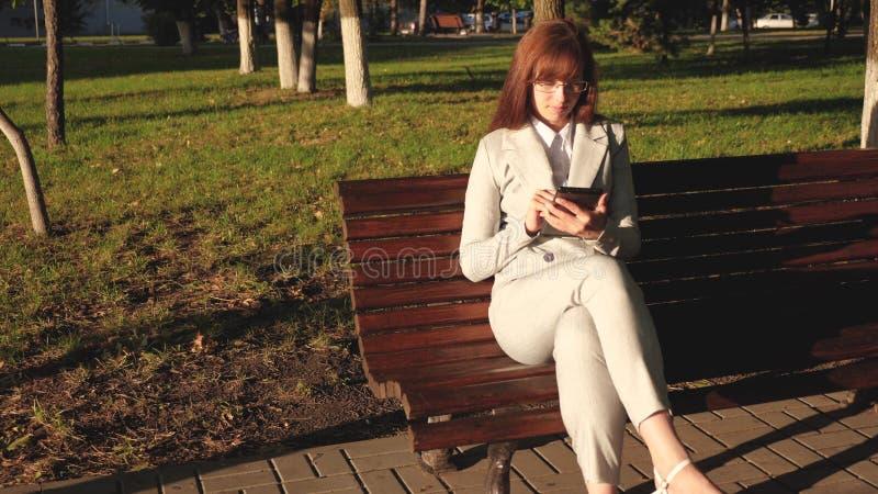 Женский бизнесмен носит стекла и работает с планшетом и проверяет электронную почту в парке лета на стенде стоковое изображение rf