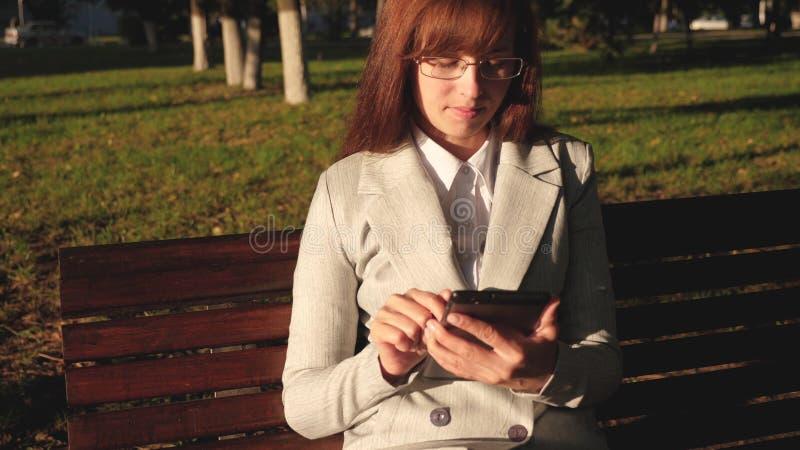 Женский бизнесмен носит стекла и работает с планшетом и проверяет электронную почту в парке лета на стенде стоковое фото rf