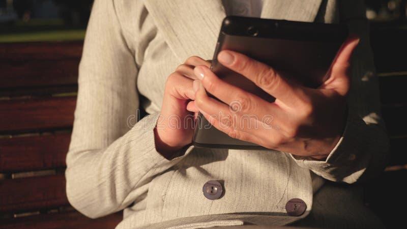 Женский бизнесмен носит стекла и работает с планшетом и проверяет электронную почту в парке лета на стенде стоковое фото
