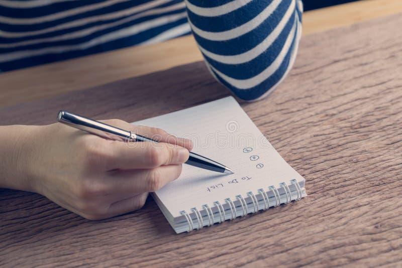 Женский бизнес-план сочинительства ручки удерживания руки сделать список на древесине стоковые изображения