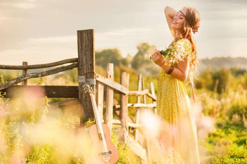 женский богемный стиль, держащий цветы на поле под закатом солнца стоковое фото