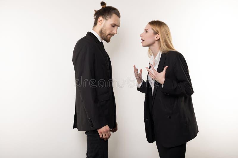 Женский босс в черном костюме бранит ее бородатого менеджера для не быть внимателен стоковая фотография rf