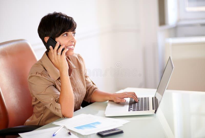 Женский босс говоря на ее мобильном телефоне стоковое фото rf