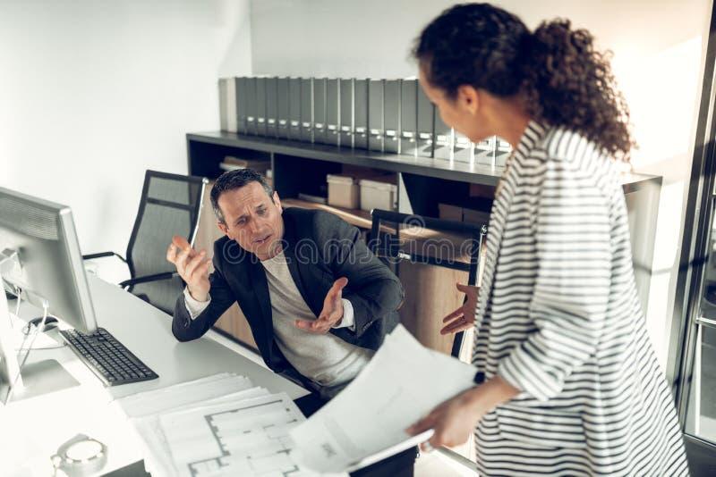 Женский босс крича на ее работнике для работы стоковое изображение rf