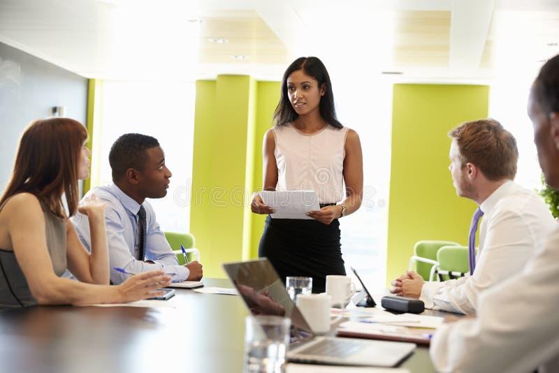 Женский босс стоит держащ документ на неофициальной встрече работы стоковое изображение rf