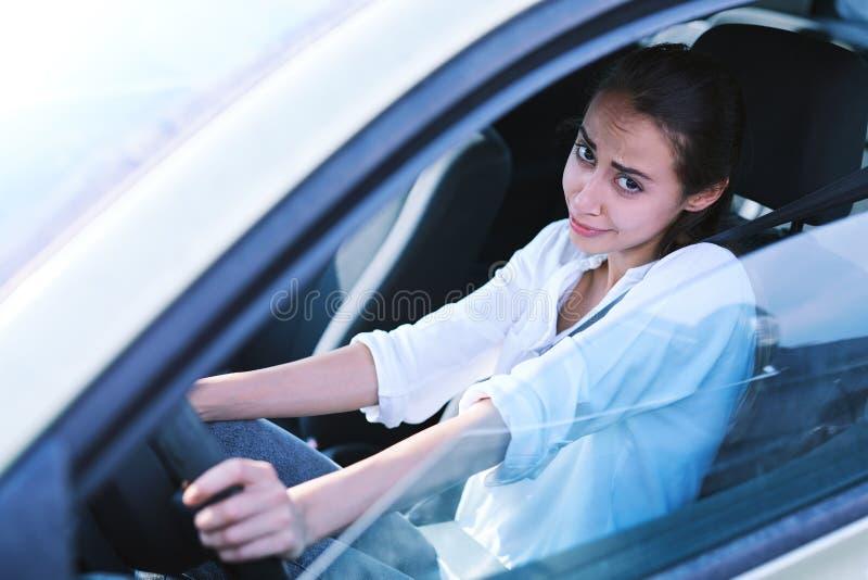 Женский водитель выглядит виновными взглядами и извиняется стоковое изображение