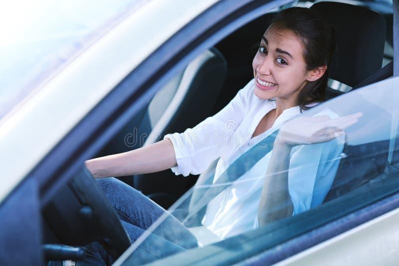 Женский водитель выглядит виновными взглядами и извиняется стоковые изображения