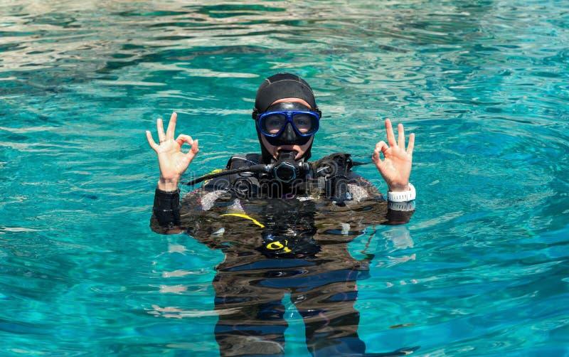 Женский водолаз акваланга показывает двойной ОДОБРЕННЫЙ знак стоковое фото