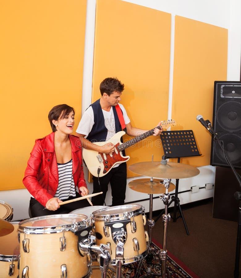 Женский гитарист барабанщика и мужчины выполняя внутри стоковое фото