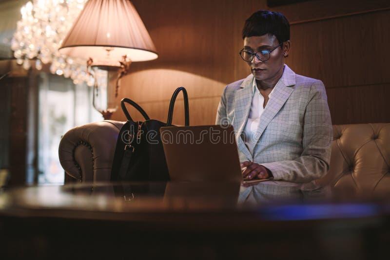 Женский главный исполнительный директор на командировке используя ноутбук в лобби гостиницы стоковые изображения rf