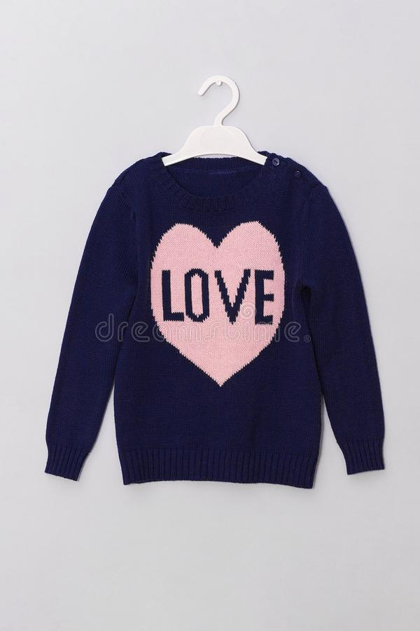 Женский голубой шерстяной свитер с сердцем пинка картины и любовью надписи на вешалке на серой предпосылке Одежды взгляда моды же стоковые фотографии rf