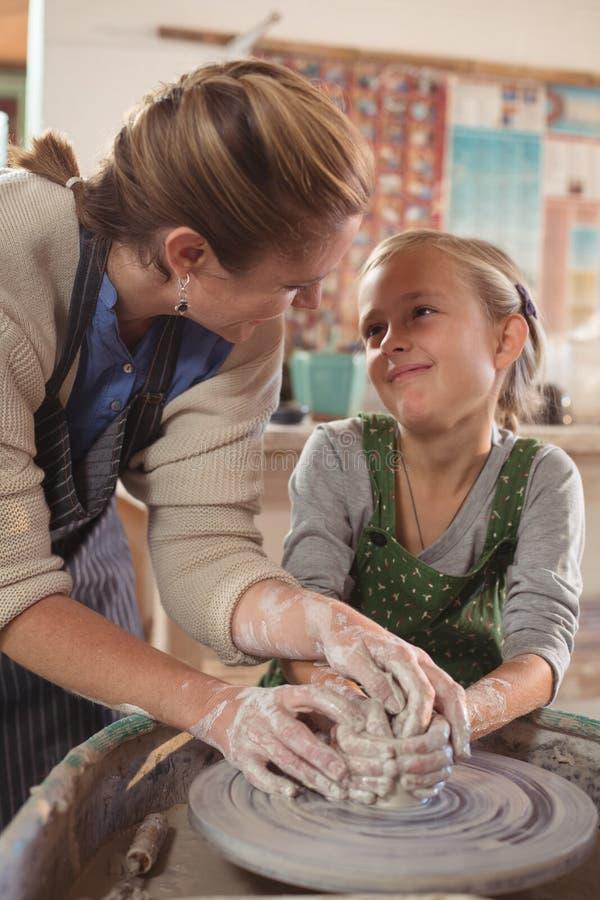 Женский гончар взаимодействуя с девушкой пока помогающ стоковое фото rf