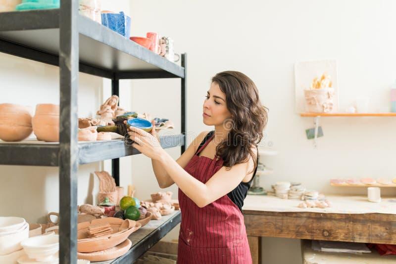 Женский гончар смотря покрашенное агашко в студии стоковые изображения rf