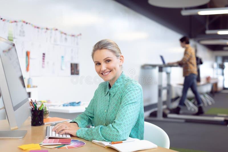 Женский график-дизайнер работая на компьютере стоковое изображение