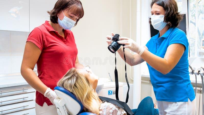 Женский дантист используя dgital камеру для того чтобы сделать фотоснимок из зубов пациентов после обработки стоковое изображение