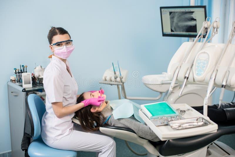 Женский дантист с зубоврачебными инструментами - отразите и прозондируйте проверять вверх по терпеливым зубам на зубоврачебном оф стоковое фото