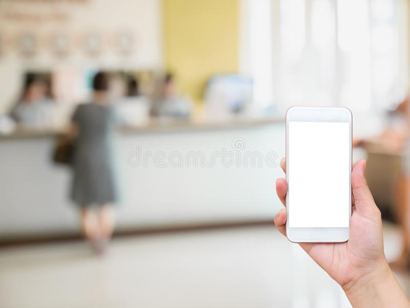 Женский держа мобильный телефон с предпосылкой приема гостиницы стоковые фотографии rf