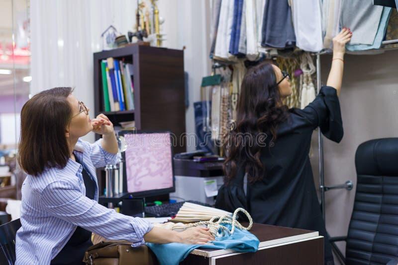 Женский дизайнер, внутренний оформитель, владелец магазина показывает ткань Магазин ткани мелкого бизнеса стоковая фотография
