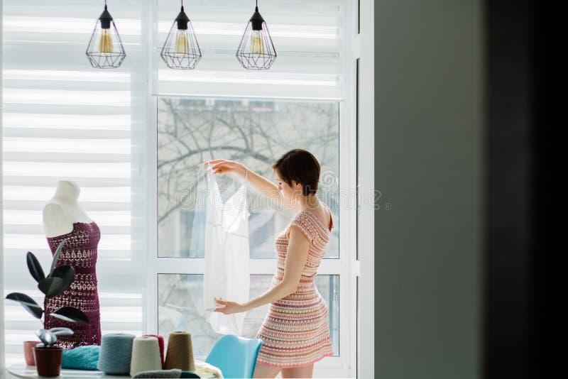 Женский дизайнер работая со связанным платьем в уютной студии внутренней, независимый, образ жизни, концепция воодушевленности стоковые изображения