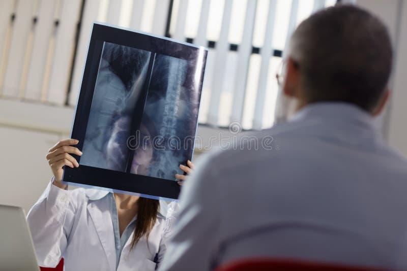 Женский доктор в стационаре с пациентом и рентгеновскими снимками стоковое изображение