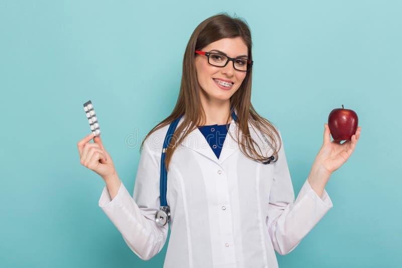 Женский доктор в стеклах с яблоком и пилюльками стоковые изображения