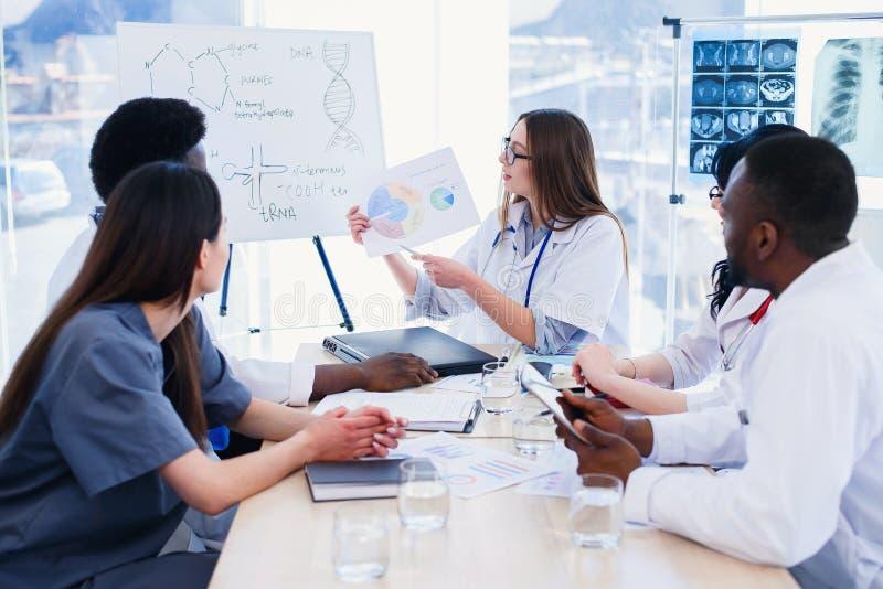 Женский доктор держа в результате луча рук x на встрече на современной клинике Профессиональные доктора multi этнической группы стоковое фото rf