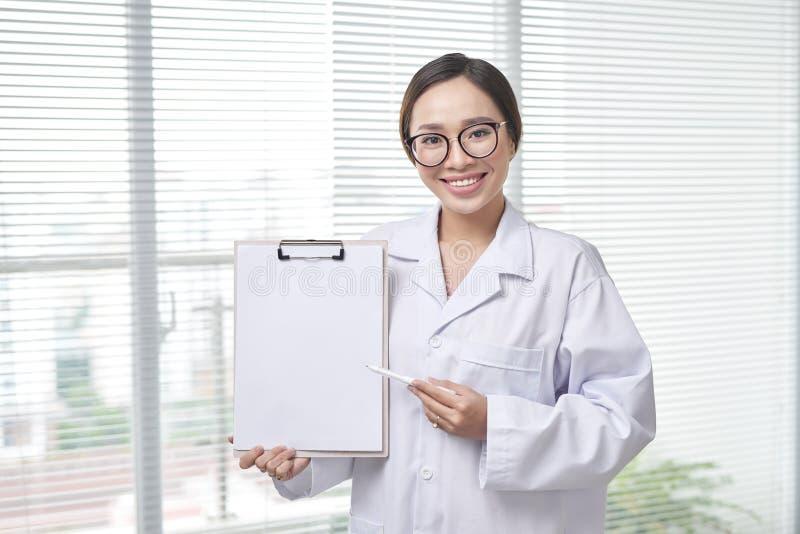 Женский доктор показывает с доской сзажимом для бумаги стоковое фото rf