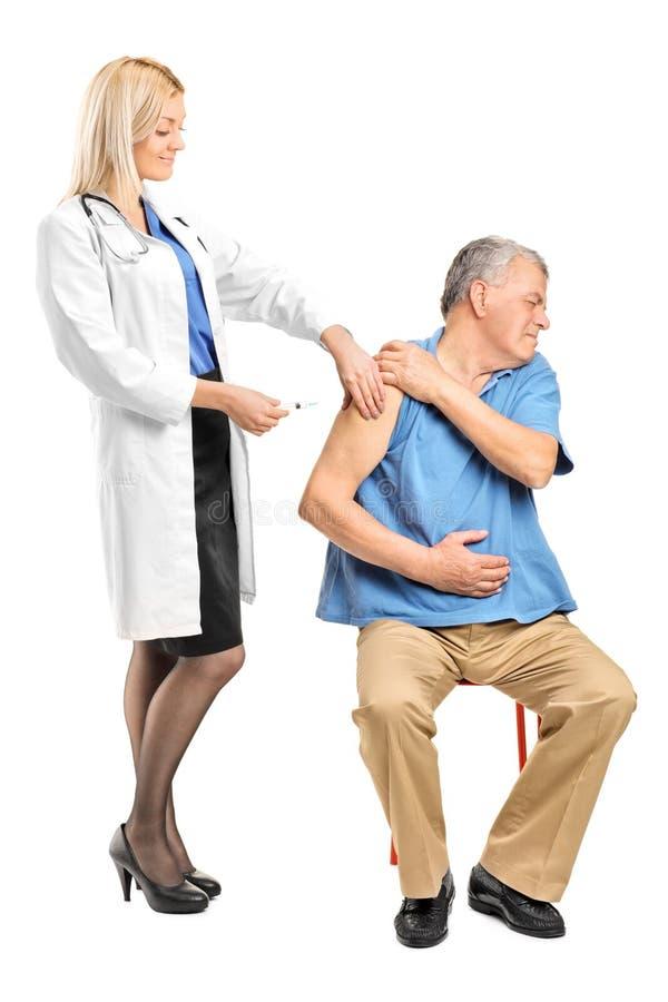 Женский доктор прикладывая шприц к пожилому человеку стоковое фото