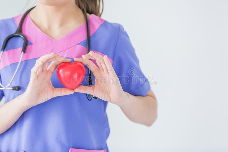 Женский доктор при стетоскоп держа красное сердце, изолированное на wh стоковое изображение