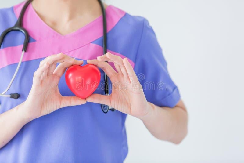 Женский доктор при стетоскоп держа красное сердце, изолированное на wh стоковое изображение rf