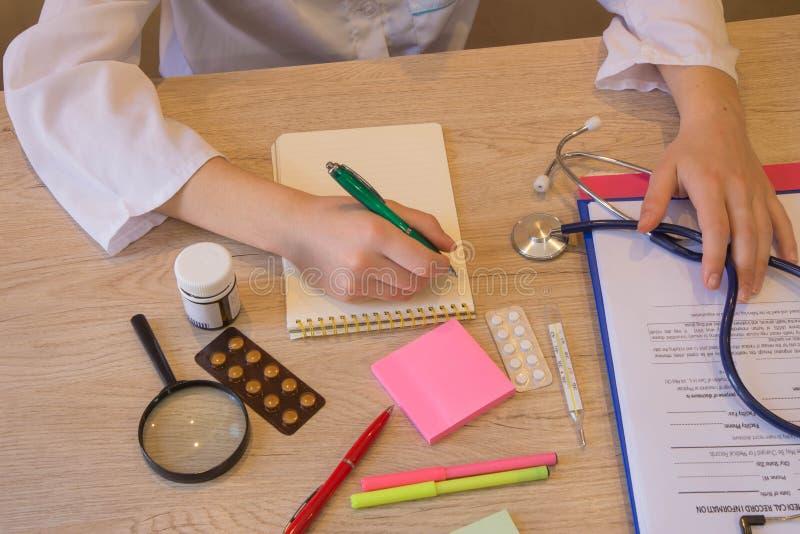 Женский доктор при стетоскоп сидя на столе, писать что-то, рецепт или рекомендацию из пациента стоковое фото