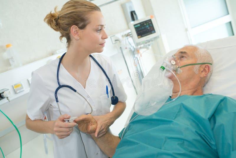 Женский доктор смотря старший мужской терпеливый нося кислородный изолирующий противогаз стоковое фото rf