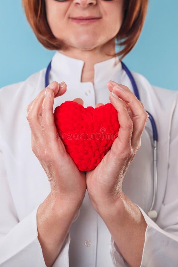 Женский доктор со стетоскопом держа сердце в ее оружиях Концепция здравоохранения и кардиологии стоковые изображения