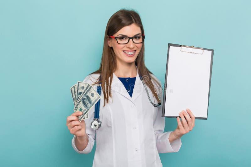 Женский доктор с вентилятором денег и доски сзажимом для бумаги стоковое изображение rf