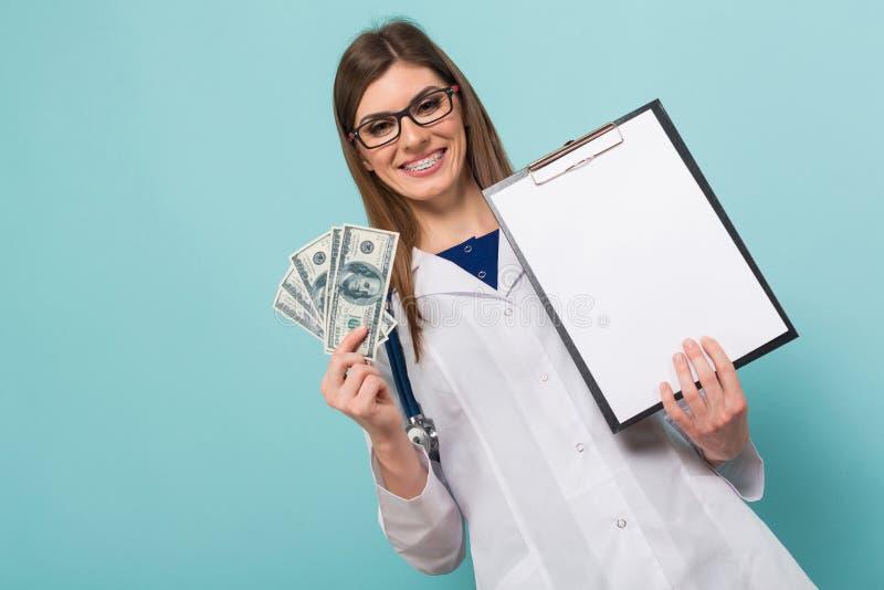 Женский доктор с вентилятором денег и доски сзажимом для бумаги стоковые изображения rf